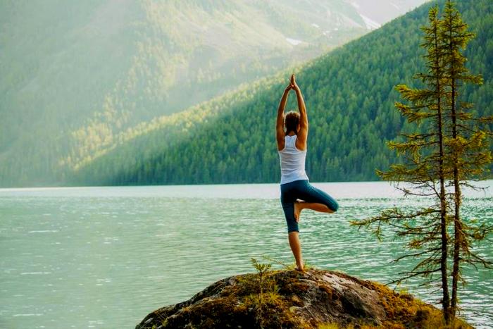 Une femme fait du yoga au bord d'un lac.